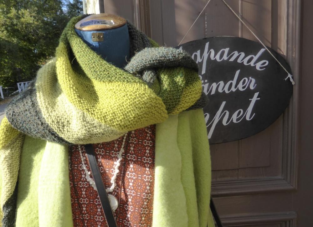 Stickad sjal på docka utanför butiken Skapande händer i Sätra brunn.